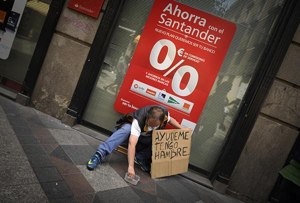 Un hombre pide limosna el 9 de junio de 2012 a la puerta de una sucursal bancaria en la calle Arenal de Madrid. Día tras día acude al mismo lugar en busca de alimento, ropa o unas monedas para alimentarse.  Pulsa sobre la imagen para ver la galería.
