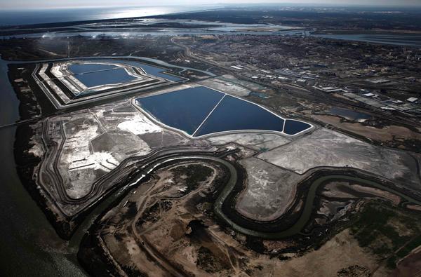 Imagen aérea de las balsas de fosfoyesos y la zona supuestamente regenerada (arriba izquierda). También puede observarse la ciudad de Huelva y apreciar la cercanía y dimensiones de las balsas. El residuo no se encuentra solo las piscinas, toda la zona gris son fosofoyesos secos. Se expulsa el residuo en estado líquido de la factoría y se almacena en esta zona. Seguidamente la evaporación lo transforma en solidó y el residuo se utiliza para levantar los diques de contención del nuevo residuo. En la zona trabajan operarios con maquinaria pesada sin protección de ningún tipo.
