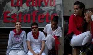 Unos jóvenes esperan el primer encierro de las fiestas de San Fermín 2013 en la curva de la calle estafeta esta mañana.  (c) Pedro ARMESTRE.  Fujifilm nos acompaña en el viaje. Pulsa sobre la imagen y podrás ver sus características.
