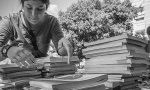 Una joven busca libros en el mercadillo de trueque de material escolar que desde Barrio del Pilar en Lucha se ha organizado para ayudar la las familias desfavorecidas. (c) Susana Hidalgo