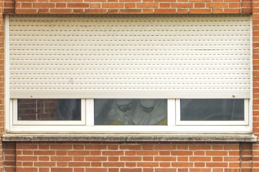 Los médicos que tratan a Teresa Romero se ven a través de la ventana del hospital Carlos III trabajando con una indumentaria no adecuada para protegerse del virus al que se enfrentan. Pulse para leer: A la caza de la villana. © Pedro ARMESTRE